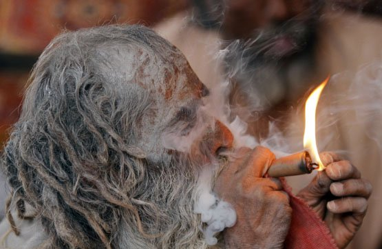 A Hindu ascetic, or Sadhu, smokes marijuana on a chillum outside the Bhavnath temple during the Mahashivratri festival in Junagadh district, in the western Indian state of Gujarat, February 20, 2012. Hindus across the country celebrate Mahashivratri, better known as the Lord Shiva's wedding anniversary. REUTERS/Amit Dave (INDIA - Tags: RELIGION SOCIETY ANNIVERSARY) - RTR2Y5D8