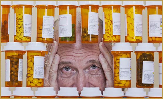 Senior man with an unhappy, depressed expression and his hands framing his face looking through an opening in rows of prescription medication. Health care and medication cost can overwhelm many senior citizens.