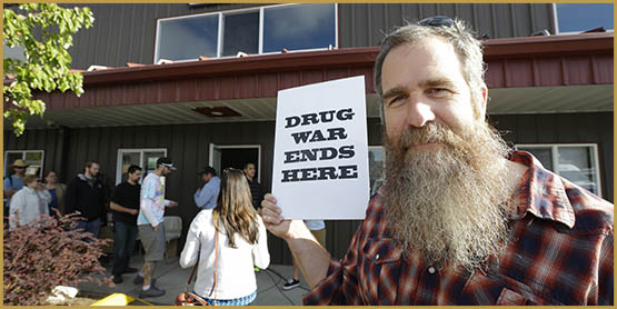 "Kevin Nelson, of Bellingham, Wash., holds a sign that reads ""Drug War Ends Here,"" outside Top Shelf Cannabis, Tuesday, July 8, 2014, in Bellingham, Wash. on the first day of legal pot sales in the state. Nelson says he is a long-time activist opposing drug laws, particularly those targeting marijuana users, and he he feels the legalization of marijuana will lead to less crowded jails and be less of a burden on the court system. (AP Photo/Ted S. Warren)"
