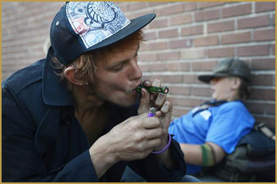 DENVER, CO. - JULY 23: Dusty Taylor, 20, left, currently homeless, smokes marijuana from a glass pipe at the intersection of 21st Ave and Stout St. in downtown Denver Wednesday morning, July 23, 2014. (Photo By Andy Cross / The Denver Post)